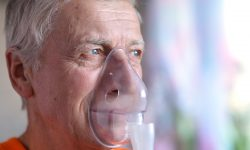 Older man mask orange top facing right
