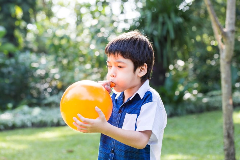 Boy blowing balloon